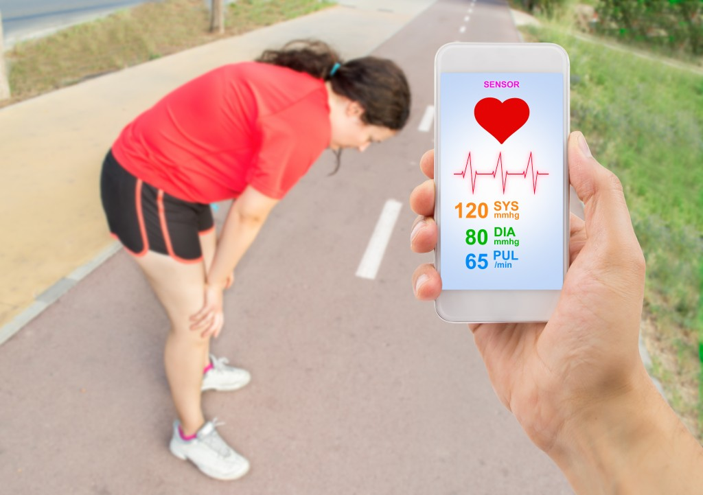 hand holding the smartphone with a healthy app and in background a woman gasping for air with her hands on her knees after a run .All screen content is designed by my and not copyrighted by others and created with digitizing tablet and image editor