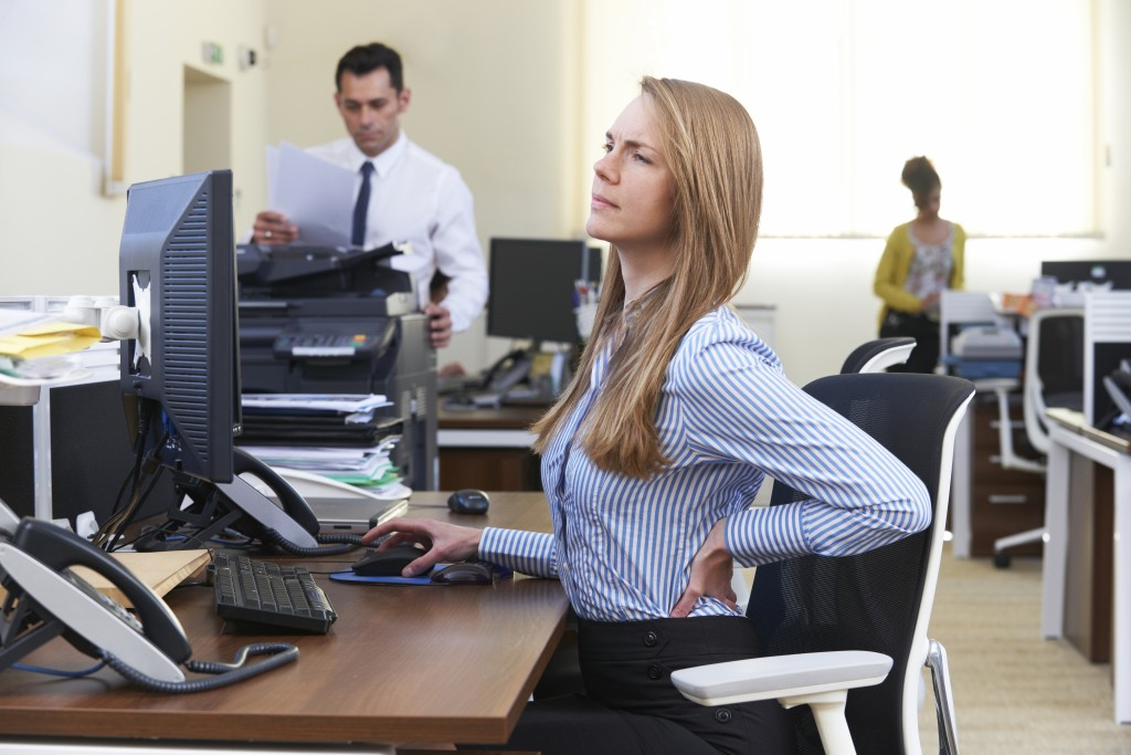 Businesswoman Working At Desk Suffering From Backache